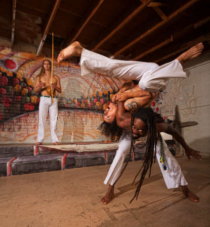 Capoeira man throwing partner over his shoulders photo