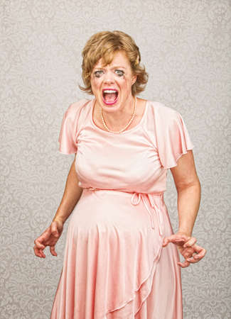 smeared mascara: Desperate pregnant person in pink dress on gray background Stock Photo