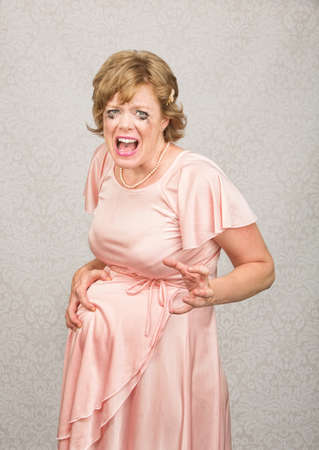 frantic: Anxious pregnant woman in pink dress on gray