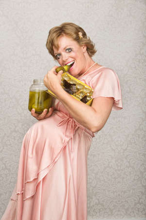 smeared mascara: Grinning pregnant lady eating candy and pickles Stock Photo