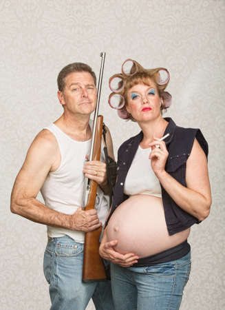 Negligente pareja hillbilly embarazada con el rifle y cigarrillos photo