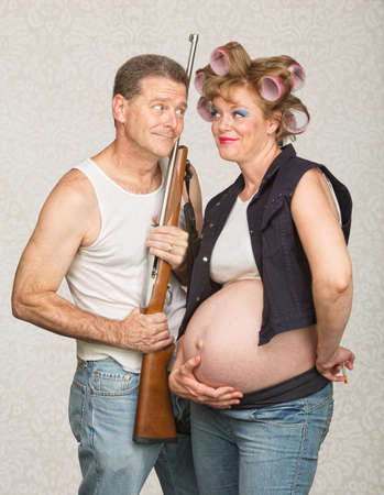 Hillbilly with rifle and adoring pregnant wife photo