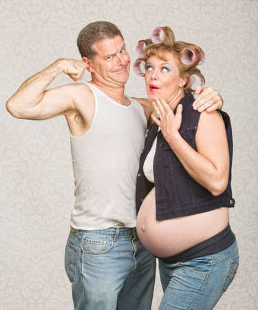 boasting: Amazed pregnant hillbilly woman and man flexing biceps