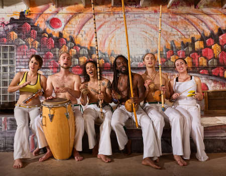 Group of six capoeira performers playing instruments and singing photo