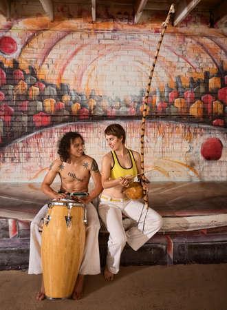 couple mixte: Mignon couple mixte dans les v�tements de capoeira jouer de la musique africaine Banque d'images