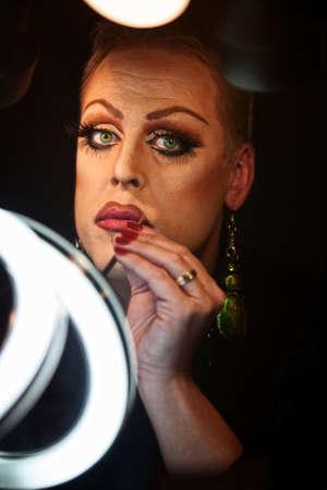Serious Caucasian drag queen using lipstick photo