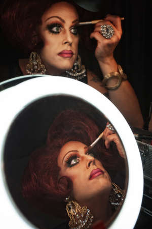Cross dressing man putting on makeup at a mirror Banque d'images