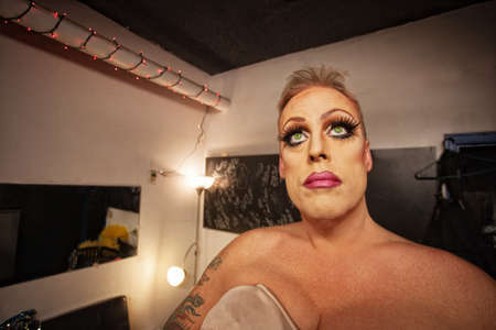 mismatch: Serious male in drag waiting in dressing room