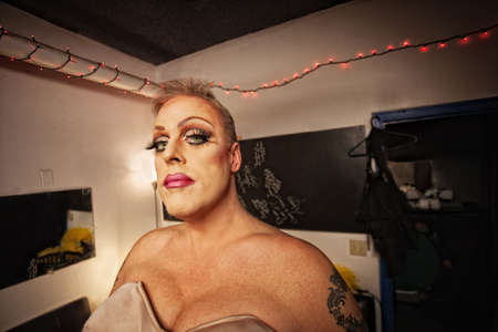 Serious drag queen with bra and tattoo in dressing room