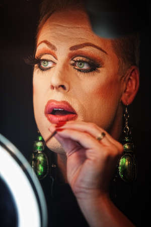 Man in drag with lipstick and mirror
