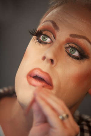 Close up of drag queen putting on lipstick