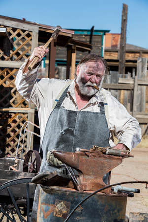 Old West Blacksmith Swings Hammer at an Anvil