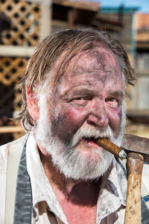 working cowboy: Old West Blacksmith Smokes Cigar While Holding Mallet