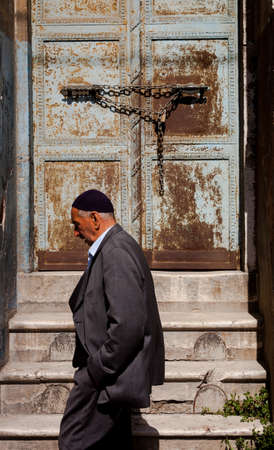 observant: ISTANBUL, TURKEY – APRIL 28: Muslim man passing by doorway prior to ANZAC day on April 28, 2012 in Ankara, Turkey.  Each year patriotic Turks honor those fallen at the battle of Galipoli during World War I.