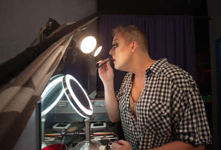 Serious male drag queen performer using lipstick pencil photo