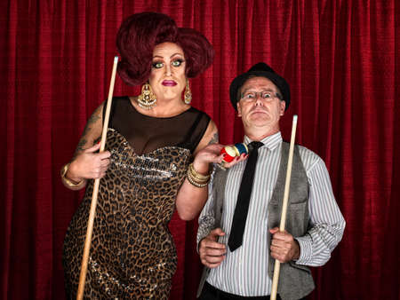 Drag queen holding pool balls with surprised man