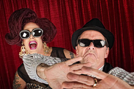 mismatch: Over-protective man in hat with surprised drag queen Stock Photo