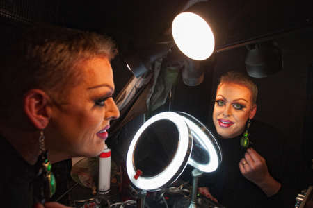 Caucasian drag queen at mirror in dressing room photo