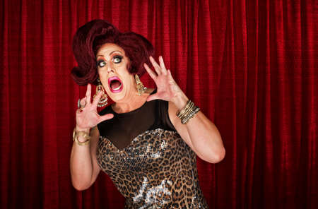 drag queen: Scared drag queen with hands up in theater