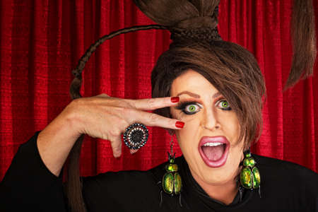 Laughing Caucasian drag queen in theater with hand near face Banque d'images