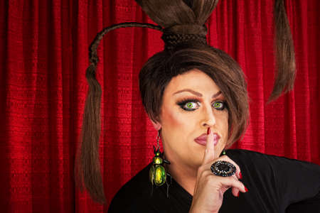 Man in drag and funny hairdo with finger near lips photo