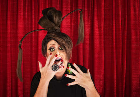 Shouting drag queen with ponytails with hands in front of mouth photo