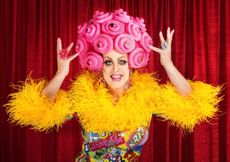 Happy man in dress and pink foam wig performing