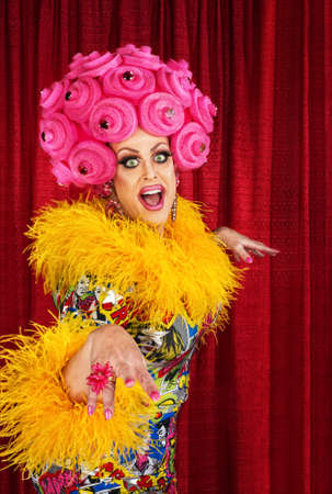 Happy dancing drag queen in pink foam wig Stockfoto