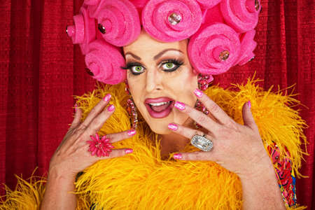 Excited white male drag queen in yellow boa