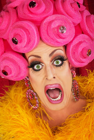 Screaming drag queen with pink foam wig in theater