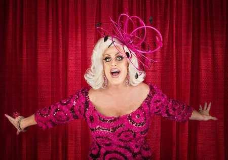 Happy drag queen in blond with singing in theater