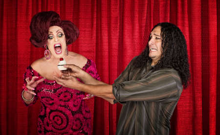 Nervous man holding cupcake for excited man in drag photo