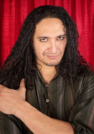deceptive: Attractive Latino man with long hair and eyeliner Stock Photo