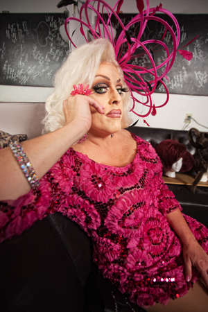 Blond drag queen in pink dress sitting on sofa
