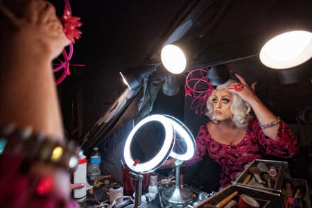 Female impersonator adjusting hair in dressing room photo