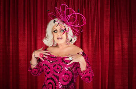 drag queen: Cute tall man in blond wig and drag over maroon curtain