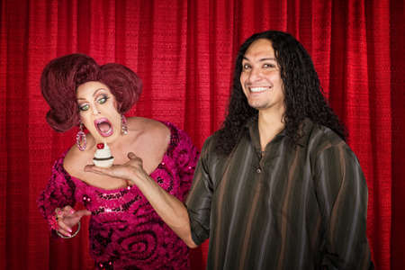 Smiling latino man with hungry drag queen and cupcake photo