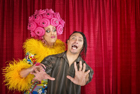 feather boa: Big drag queen trying to kiss a scared man Stock Photo
