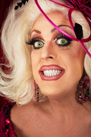Smiling blond drag queen with big eyelashes