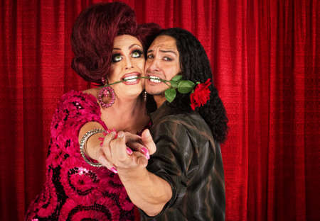 Embarrassed man with rose in mouth dancing with drag queen
