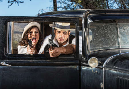gangster with gun: 1920s vintage gangsters in shoot out behind car door Stock Photo