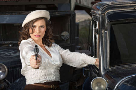 tough woman: Retro 1920s era female gangster aiming gun next to car
