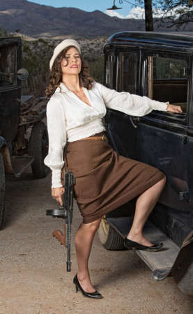 Beautiful 1920s gangster woman with gun next to car