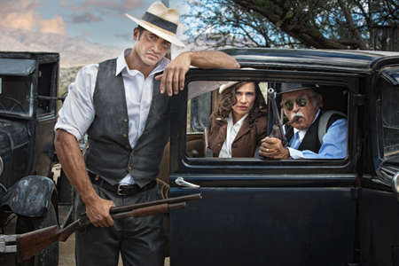 antique rifle: Handsome 1920 era gangsters with pretty woman Stock Photo
