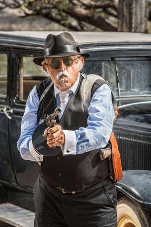 firing: Dangerous male gangster with cigar firing machine gun
