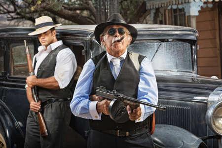 Ernstige maffiabaas met pistool en bewaker in de buurt van de auto Stockfoto