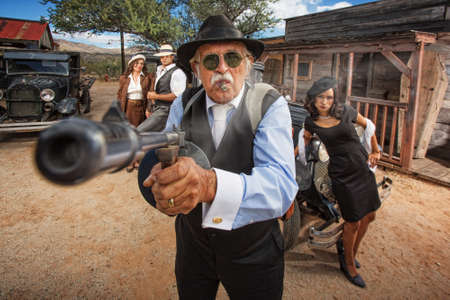mature mexican: 1920s vintage gangsters outside shooting machine gun