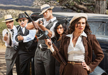 tommy: Pretty woman with submachine and gangsters by car Stock Photo