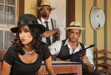 Serious gangster woman with bootleggers at table photo