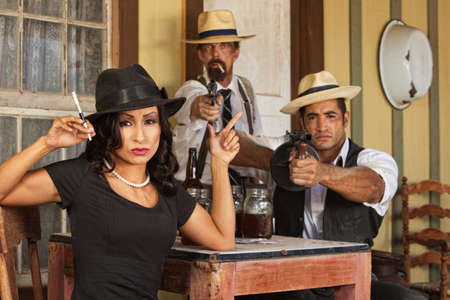 Pretty woman gesturing a gun with whiskey bootleggers photo